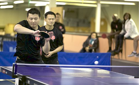 One man hit a table tennis ball as another man looks on