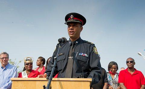 An officer in uniform stands behind a podium.