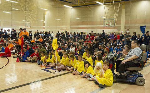 A group of hundreds of seated children and standing adults in a gym