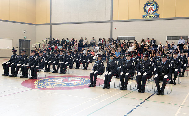 Large group of men and women, some in uniform, are seated in a gymnasium environment