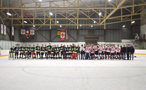 A group of boys in hockey uniform lined up at centre ice