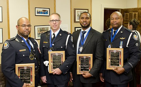 Three men in TPS dress uniforms and one man in a suit holding plaques