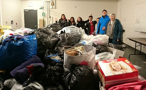 A large pile of bags with people standing in rear