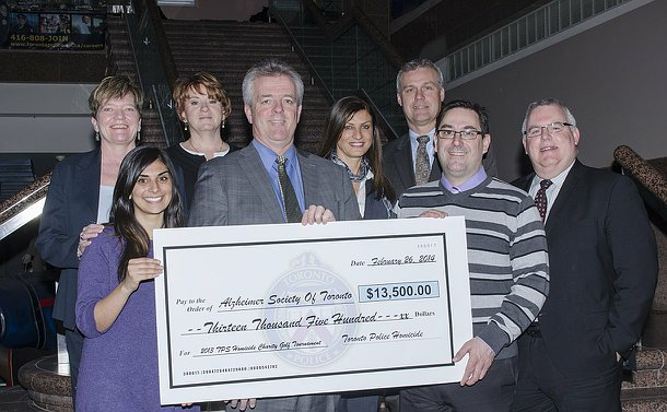 A group of people holding an oversized cheque