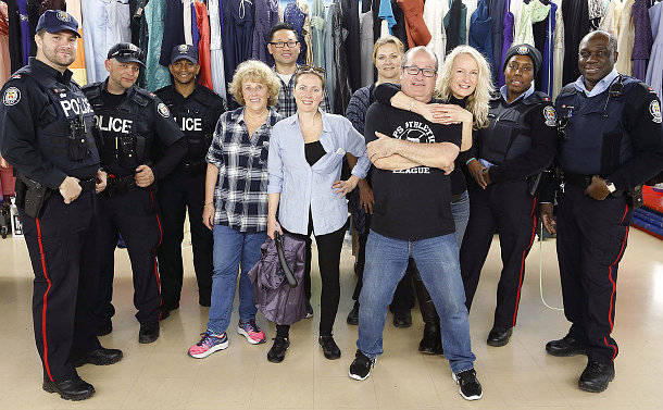 A group of men and women, some of them in police uniforms stand in-front of a long rack of various articles of clothing