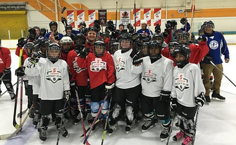A group of a people in hockey uniform on a rink