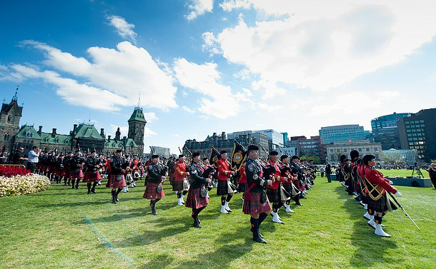 Pipe band members in different uniforms with instruments in hand, marching by the parliament building.
