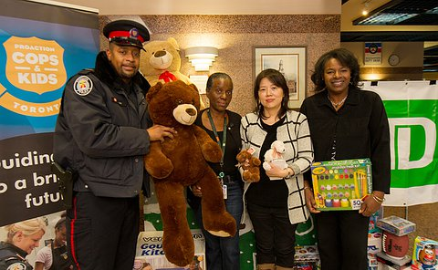 A man in TPS uniform with three women holding stuffed animals and toys standing amongst other toys
