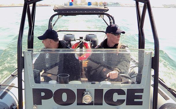 Two men in TPS uniform in a boat