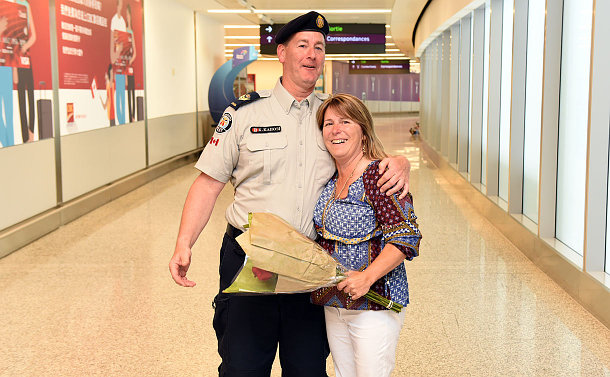 Man in a uniform and a woman holding a bouquet of flowers, hugging.