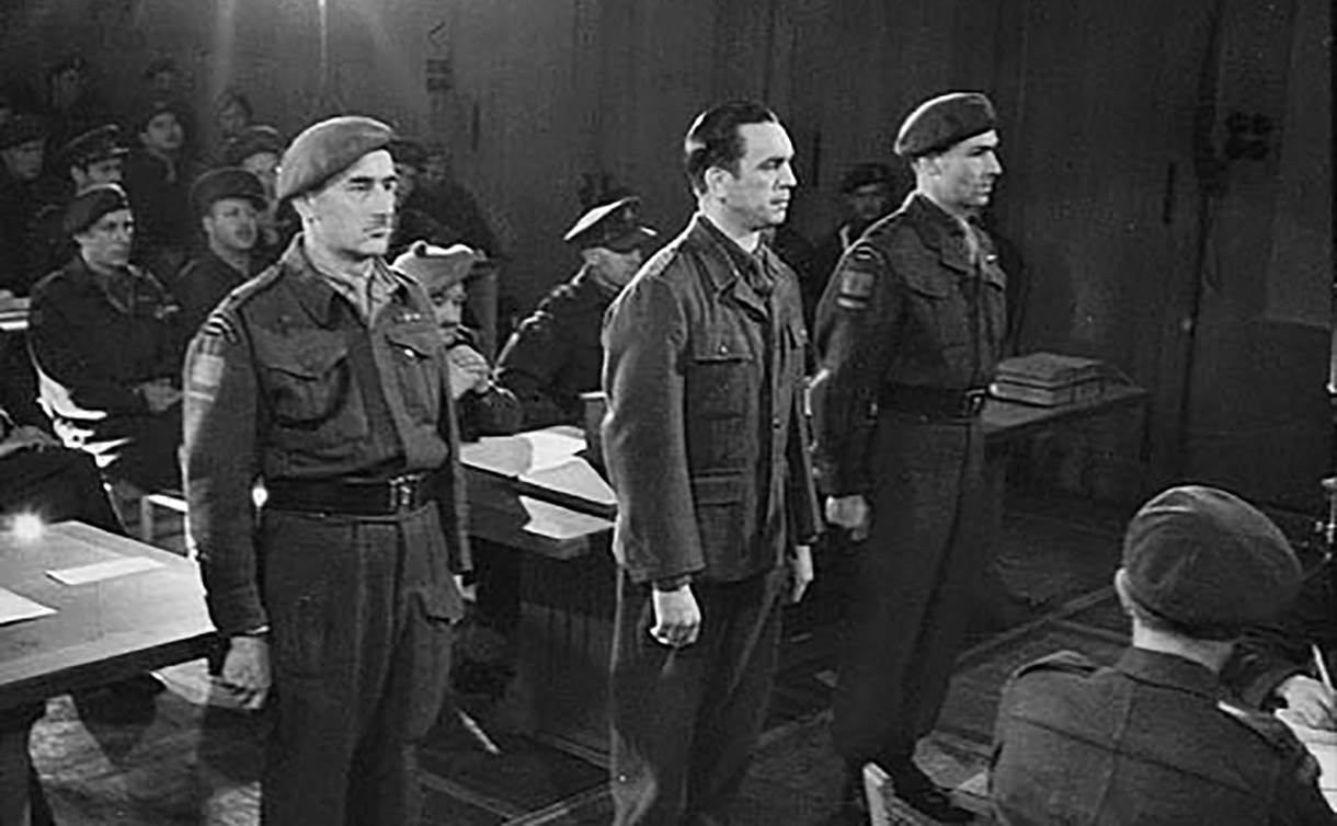 Three men standing in a courtroom