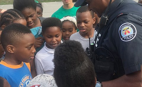 A man in TPS uniform is surrounded by children
