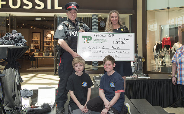 A man in TPS uniform holding a large cheque with a woman, two boys kneel in front of them