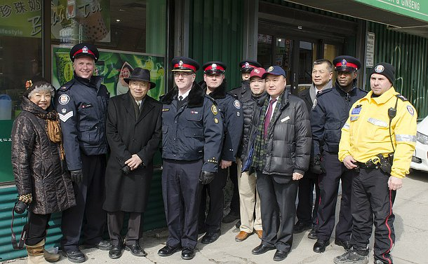 A group of people including men in TPS uniform on a street corner