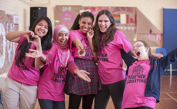 A group of girls in pink T-shirts in a school gym