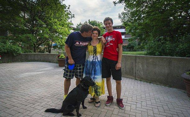 A man, woman and teenage boy with a dog on a leash