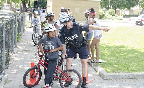 An officer in uniform kneeling next to a child on a red bicycle pointing in the distance as the child looks on.