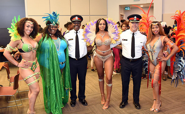 Two men in police uniforms stand among four women dressed in carnival costumes