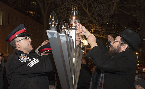A man in TPS uniform with another man lighting a large menorah candle