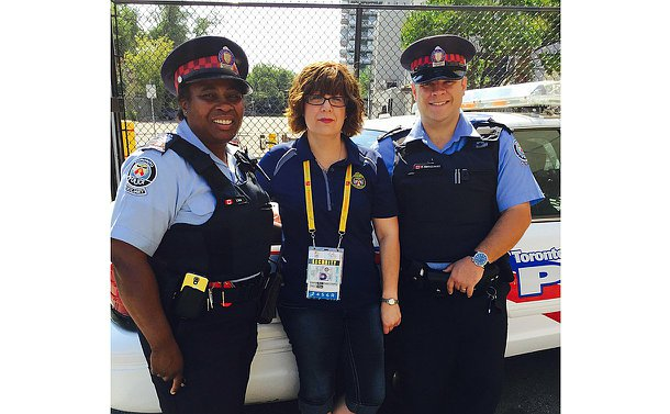 A man and woman in TPS Auxiliary uniform with a woman in a TPS golf shirt