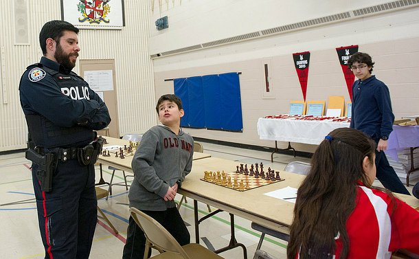 A man in TPS uniform speaks to a boy sitting near a chess board