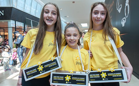 Three girls in yellow T-shirts holding donation boxes
