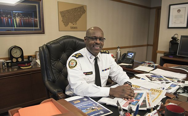 A man in TPS uniform seated at a desk