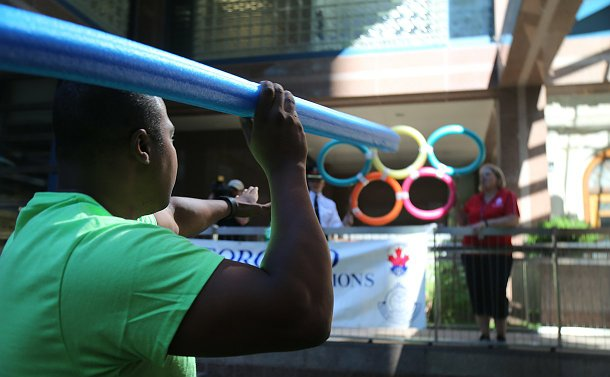 A person holds a pool toy aiming at Olympic rings