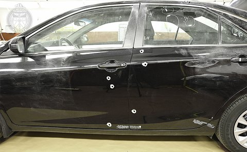 A black car with bullet holes in the driver's side