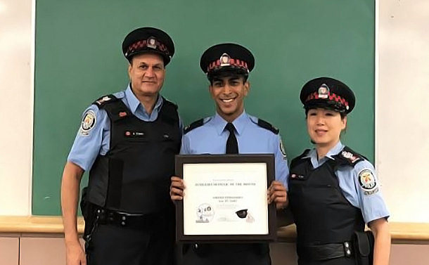 Two men and one woman wearing auxiliary police officer uniforms; man in the middle is holding an award