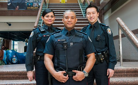 Two men and one woman wearing TPS uniforms with small cameras on their chests standing on a staircase