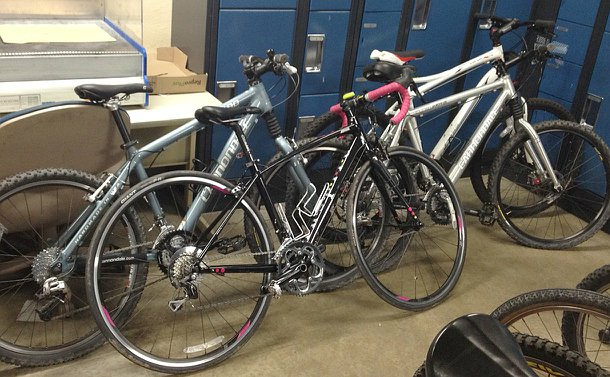 Four bicycles leaning against a storage lockers