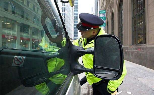 A man in TPS uniform reaches over a car hood and looks in the windshield