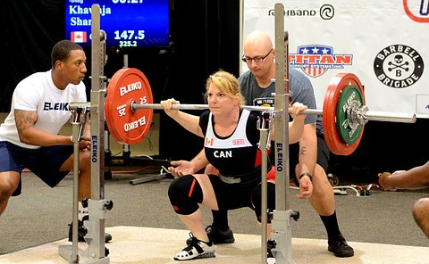 A woman with a weighted bar over her shoulders as two men spot her nearby