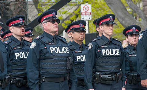 A row of TPS members standing looking ahead, with one man in the middle looking directly at the camera.