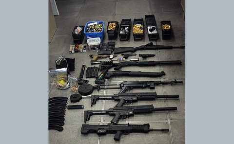 A large quantity of ammunition, guns and drugs laying on the floor.