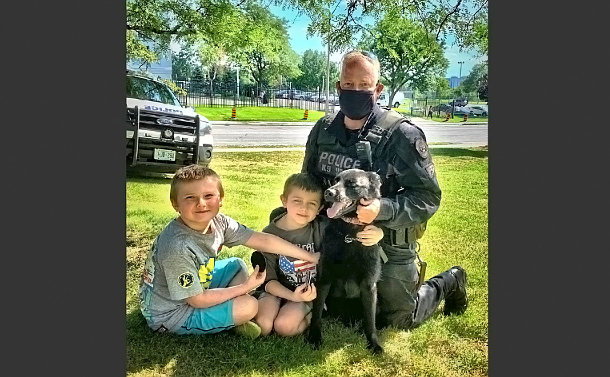 Two young boys, a man in a police uniform, and a dog