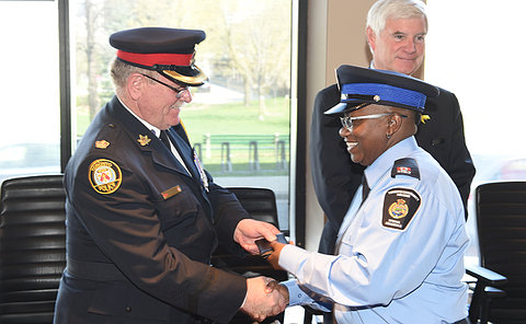 A man in TPS uniform hands over a wallet to a woman in TCH uniform