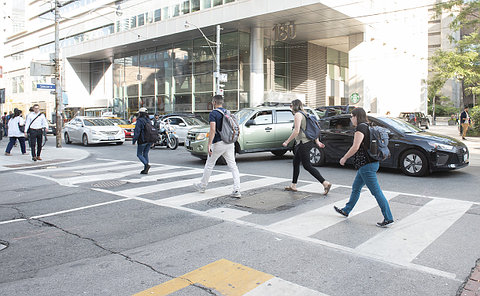 A car turning as pedestrians cross an intersection