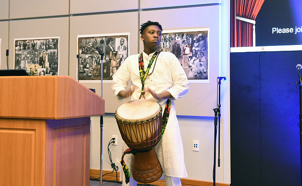 A student playing a drum
