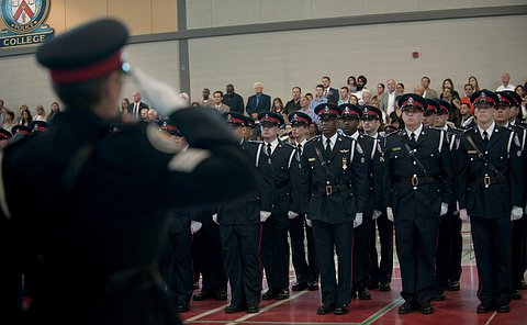 Toronto police officers in full uniform stand up, while in the foreground a female officer is saluting