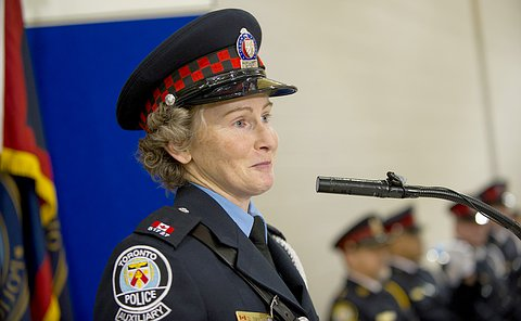 A woman in auxiliary uniform speaking at a podium.