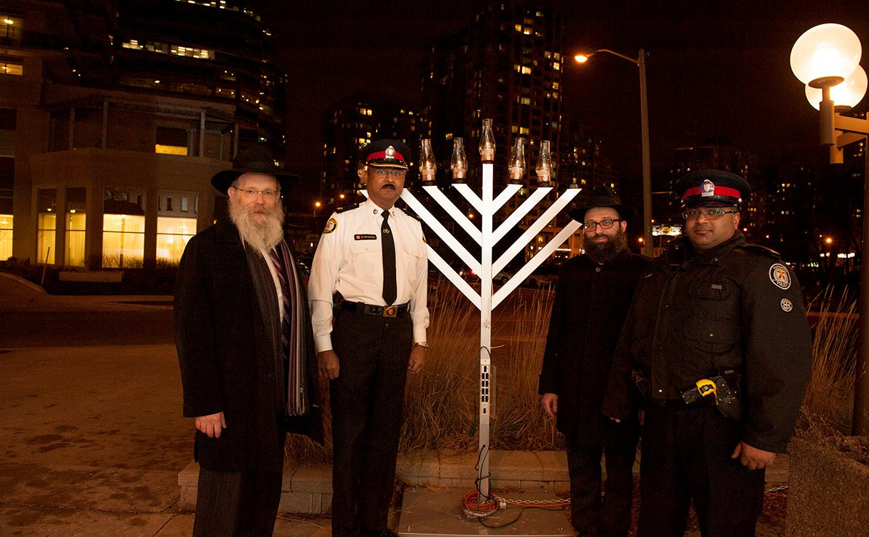 Two men in TPS uniform and two other men stand beside a menorah larger than themselves