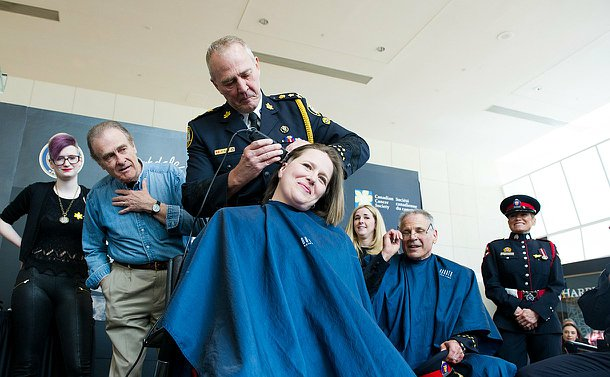 The chief using a shaver to shave of a female constables hair as people look on