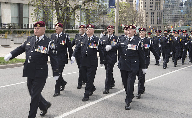 Group of men and women wearing police uniforms, many with numerous decorations, marching in unison on the street