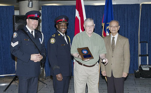 Two men in uniform, the Board Chair and an older gentlemen pose.