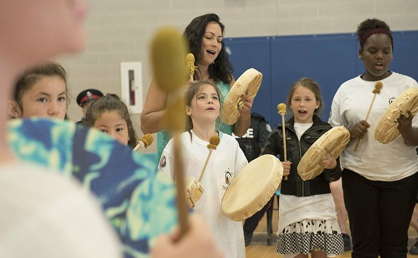 A group of girls and women singing, holding hand drums