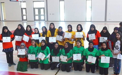 Several rows of girls, many in headscarves hold paper certificates