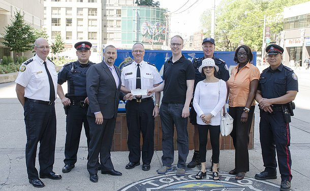 A group of men and women, some in TPS uniform, in front of a TPS sign. Three men hold a cheque