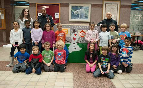 A box with a snowman on it, on either side of the box are students aged 7-9 and a teacher along with two officers in uniforms. All are smiling and looking at the camera.